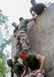 A group of soldiers are helping each other to climb over a tall military obstacle.