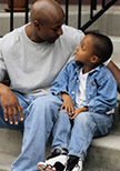 An African-American father is talking to his child by the front-door staircase.